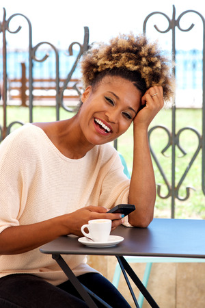 Portrait of african woman with mobile phone in coffee shop
