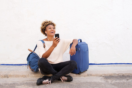 Portrait of traveling young woman sitting on sidewalk with suitcase and listening to music