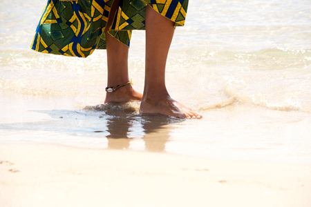 Portrait of african female feet standing on the sea shore