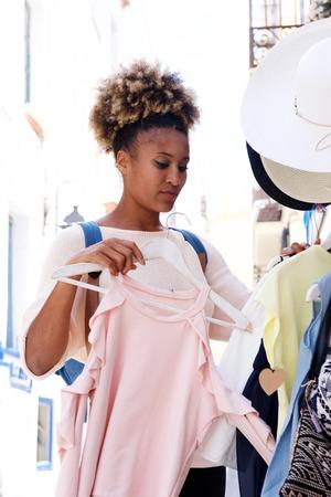 Portrait of afro american woman choosing dress in clothing store Lizenzfreie Bilder