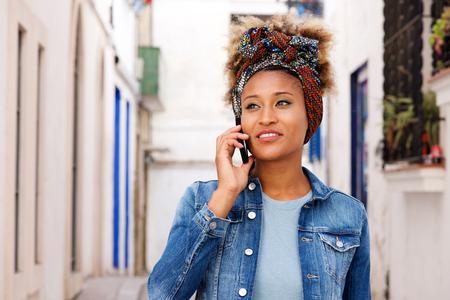 Portrait of african female  model walking on the street and talking on smart phone Lizenzfreie Bilder
