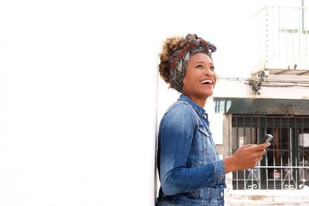 Portrait of stylish black female standing outdoors with smart phone Lizenzfreie Bilder