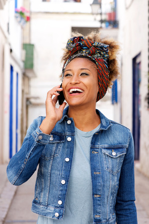 Portrait of smiling young african woman making phone call outdoors