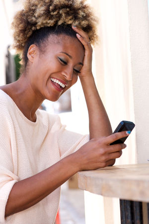 Portrait of smiling african american woman reading text message on mobile phone outdoors