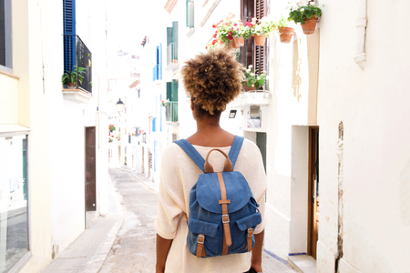 Rear view portrait of african american woman walking on the narrow street with bag