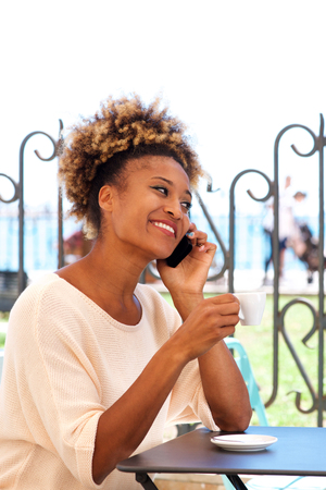 Portrait of african young woman sitting in coffee shop and talking on cellphone