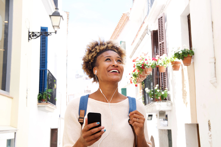 Portrait of african american woman walking down the street and listening to music on mobile phone Lizenzfreie Bilder