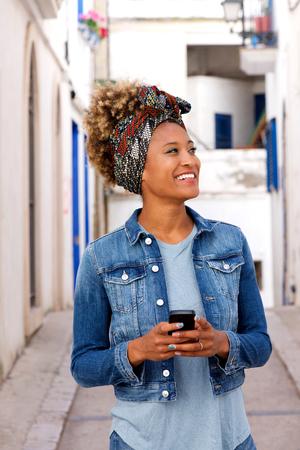 Portrait of trendy black female walking outdoors with mobile phone and looking away Lizenzfreie Bilder