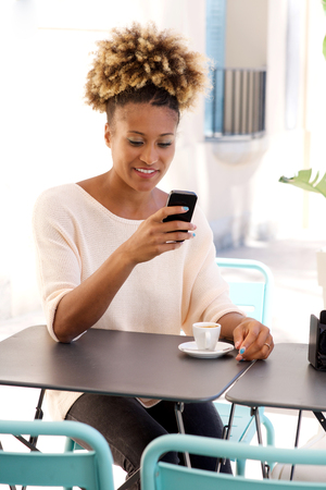 Portrait of african woman sitting at outdoor cafe looking at mobile phone