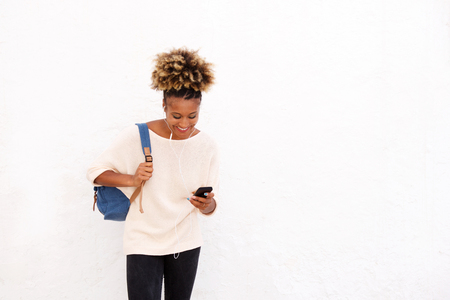 Portrait of young afro woman looking at mobile phone on white background Lizenzfreie Bilder