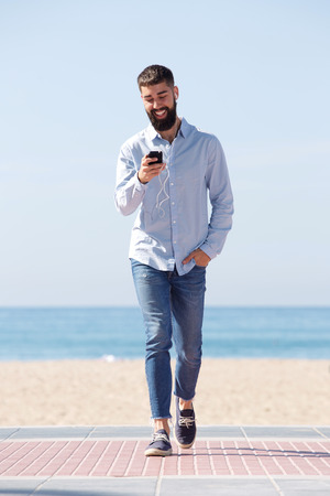 Full length portrait of smiling man walking with mobile phone listening to music