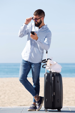 Full length portrait of man standing on beach with suitcase and mobile phone