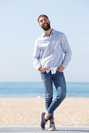 Full length portrait of confident man laughing and standing on beach Stock Photo