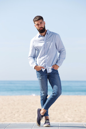 Full length portrait of serious handsome man standing by beach posing