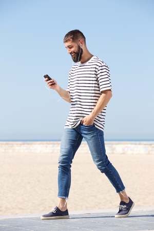 Full length portrait of happy man in earphones walking on beach with mobile phone Stock Photo