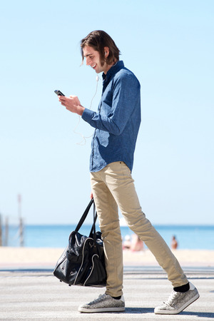 Full length side portrait of happy man standing by sea with phone and bag