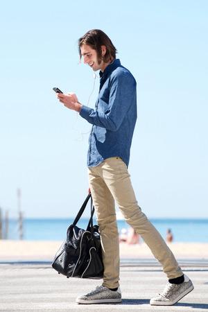 Seitenporträt in voller Länge des bereitstehenden Sees des glücklichen Mannes mit Telefon und Tasche Standard-Bild - 87636344
