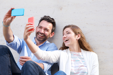 Close up portrait of happy couple holding cellphones and taking selfies