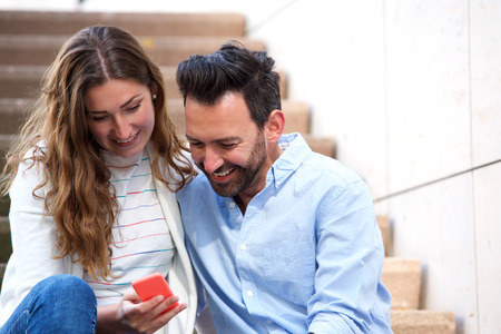Close up portrait of cheerful couple sitting on steps together with mobile phone