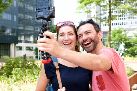 Close up portrait of happy couple taking self portrait outside with camera