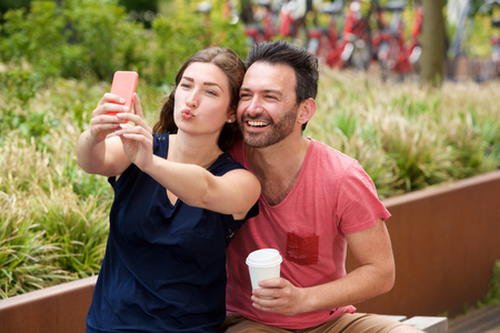 Portrait of happy young couple sitting together taking selfie on smart phone