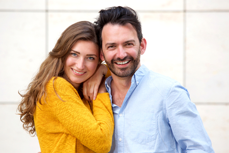 Close up portrait of romantic couple standing together in embrace smiling Lizenzfreie Bilder