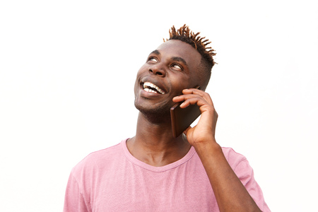 Close up portrait of happy young black guy standing against white background and making phone call