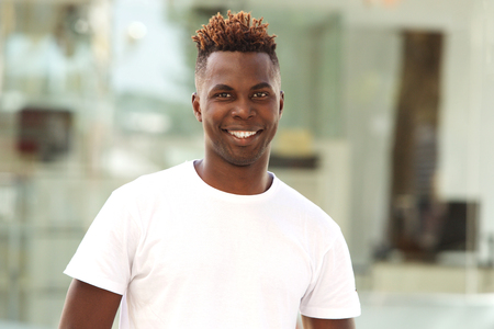 Portrait of smiling young african american man standing outside in the city