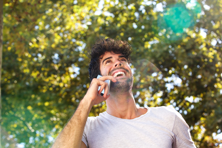 Close up portrait of laughing man talking on mobile phone outside in autumn