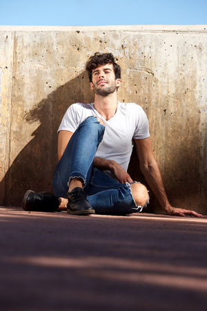 Full body portrait of happy man sitting by concrete wall with eyes closed