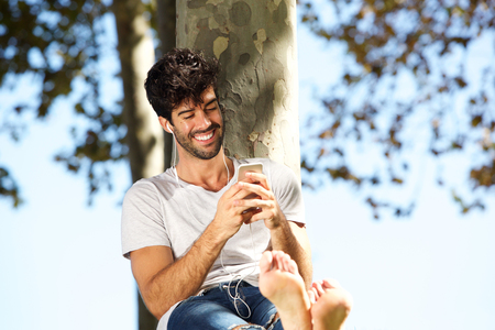 Portrait of smiling man sitting by tree barefoot with headphones and cellphone