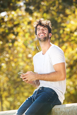 Portrait of happy man sitting on wall in park with cellphone