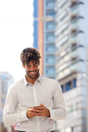 Portrait of happy man standing in city with mobile phone