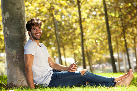 Full body portrait of happy man sitting in grass with cellphone and headphones Lizenzfreie Bilder