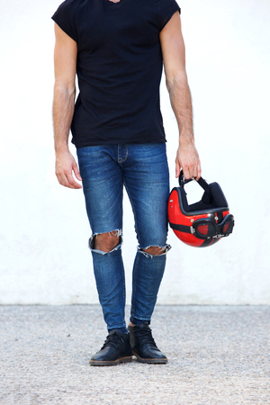 Low portrait of motorcyclist in ripped jeans holding helmet
