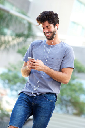 Portrait of happy man standing with headphones holding smart phone