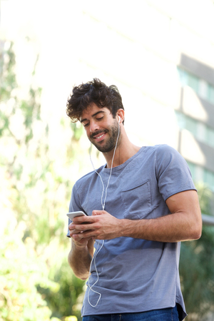 Portrait of smiling man standing with headphones holding smart phone