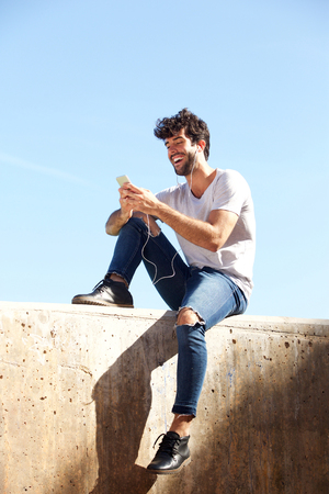 Full body portrait of cheerful man sitting on wall with headphones and cellphone