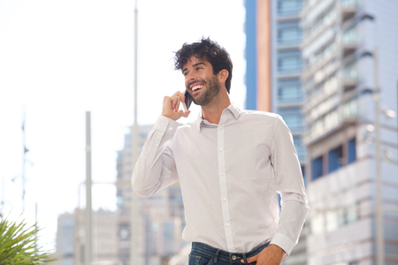 Side portrait of happy man laughing and talking on smart phone outside
