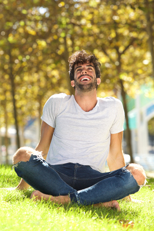Full body portrait of handsome man sitting outside in grass leaning back laughing