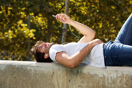 Portrait of happy man lying on wall in park with cellphone