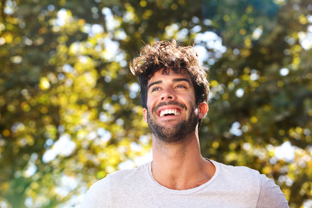 Close up portrait of laughing handsome man with beard outside in nature