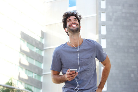 Portrait of cheerful man walking in city with headphones and mobile phone Lizenzfreie Bilder