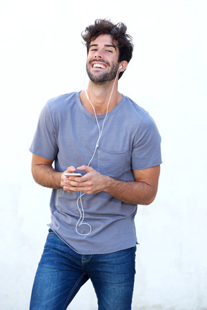Portrait of happy man holding mobile phone listening to music
