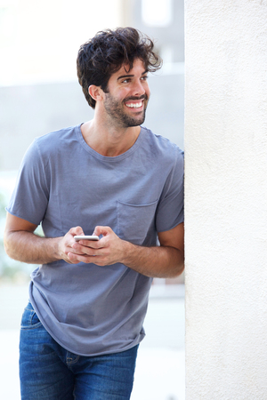 Side portrait of happy man holding phone leaning on wall outside