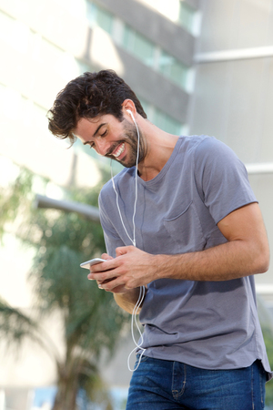 Portrait of laughing man standing with headphones holding smart phone