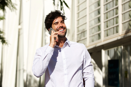 Portrait of laughing man talking on mobile phone outside in city Lizenzfreie Bilder