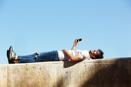 Full body portrait of cheerful man lying on wall with headphones and cellphone