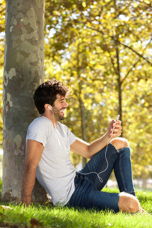 Full body portrait of laughing man sitting outside with cellphone and headphones