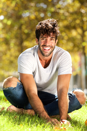 Full body portrait of handsome man sitting outside in grass leaning forward laughing Lizenzfreie Bilder